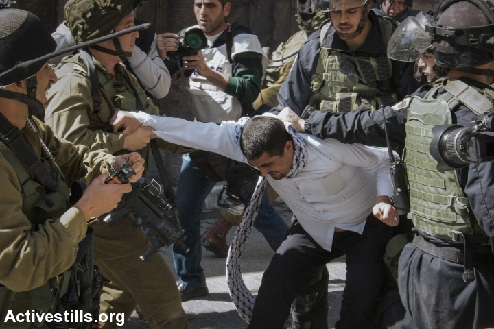 Israeli soldiers arrest a Palestinian man during a protest against the closure of the Shuhada street to Palestinians, in the West Bank city of Hebron, February 27, 2015. (photo: Miki Kratsman/Activestills.org)