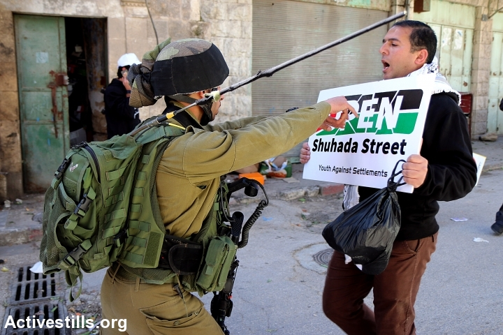 Palestinians protest against the closure of Shuhada Street, Hebron, West Bank, February 27, 2015. Hundreds of Palestinians and internationals gathered on Friday marking the 21th anniversary of the street's closure. (photo: Ahmad al-Bazz/Activestills.org)