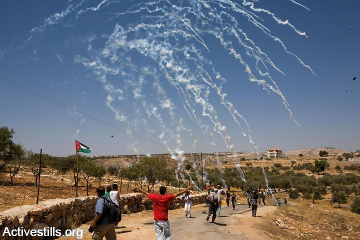 Protesters run for cover after Israeli soldiers shoot tear gas during a demonstration in Bil'in. (photo: Keren Manor/Activestills.org)