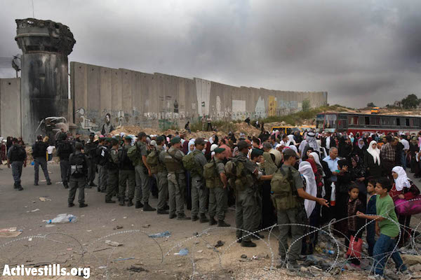 Palestinians wait to cross into Israel at the Qalandiya checkpoint outside the West Bank city of Ramallah. (Photo by Oren Ziv/Activestills.org)