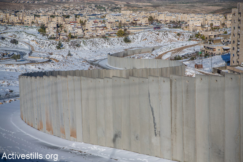 Snow around the separation wall that surrounds the Shuafat Refugee Camp in East Jerusalem, February 20, 2015. (Photo by Yotam Ronen/Activestills.org)