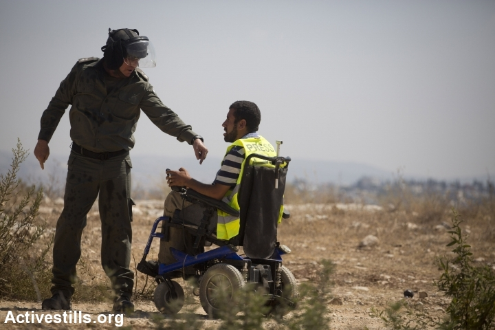 An Israeli soldier speaks to a wheelchair-bound Palestinian protester during a demonstration in Bil'in. (photo: Oren Ziv/Activestills.org)
