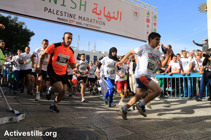 Runners cross the start line in Bethlehem's Manger Square during the third annual Palestine Marathon, March 27, 2015.