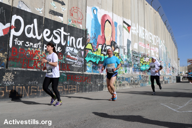 Runners pass graffiti on the Israeli Separation Wall dividing the West Bank city of Bethlehem in the third annual Palestine Marathon, March 27, 2015.