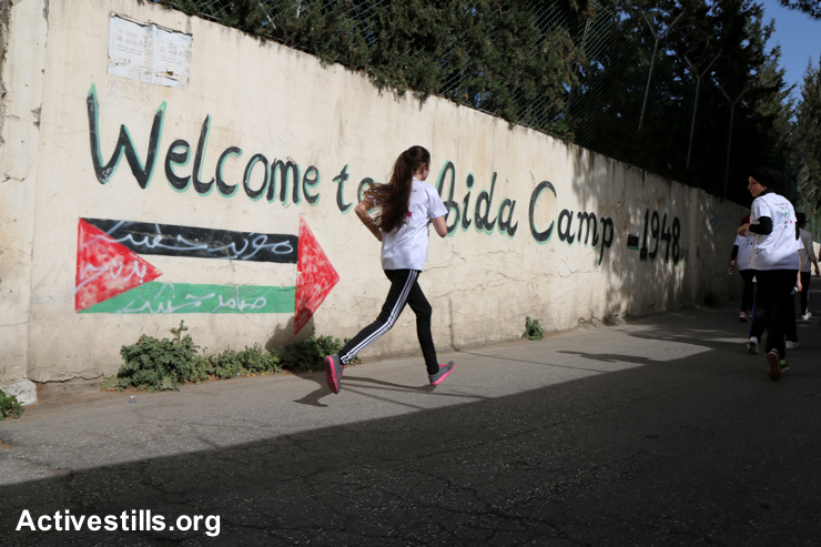 Palestinian and international runners pass through Aida Refugee Camp during the third annual Palestine Marathon, March 27, 2015.