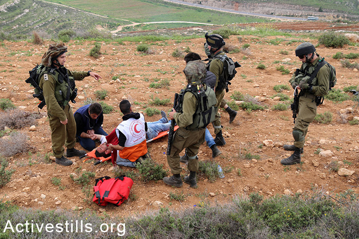 Palestinians try to treat an unconscious Palestinian in the village of Qaryut. Soldiers refused him treatment and decided to arrest and remove him in a military jeep.  (photo: Activestills.org)