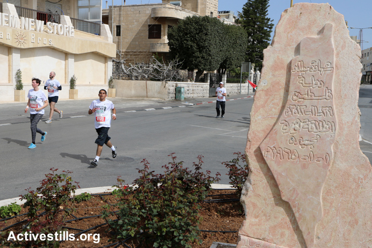 Palestinian and international competitors run along Bethlehem's Manger Street during the third annual Palestine Marathon, March 27, 2015.