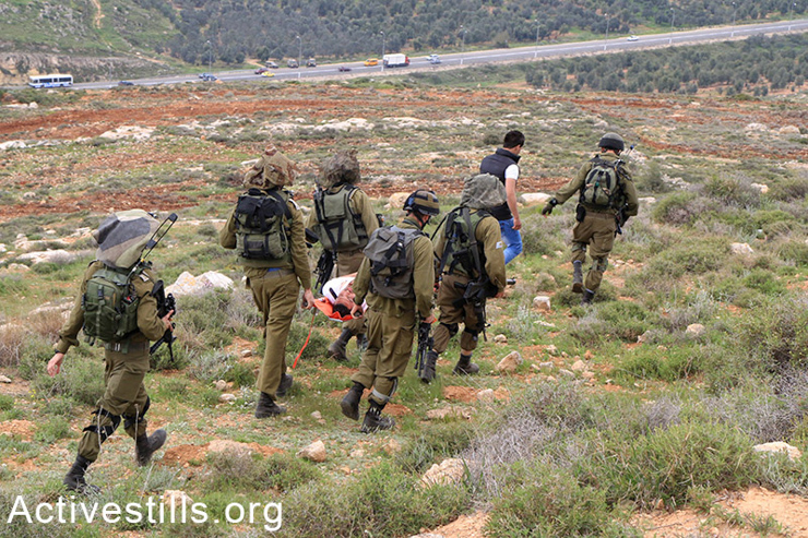 Israeli soldiers take away two Palestinians they've arrested, one of them while unconscious. (photo: Activestills.org)