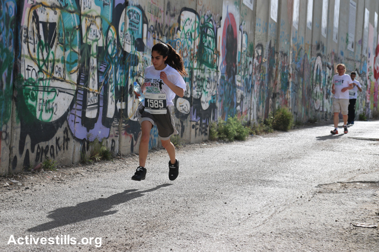 Runners race along the Israeli separation wall dividing the West Bank city of Bethlehem in the third annual Palestine Marathon, March 27, 2015.