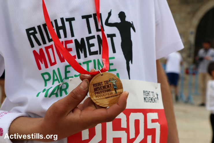 A participant shows off his olive-wood participants' medals following the third annual Palestine Marathon, March 27, 2015.