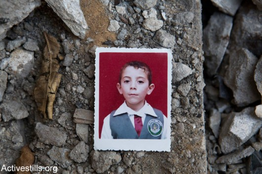 A photo of Abdallah Abdel Hadi Al Majdalawi amid the ruins of his home, Gaza Strip, March 19, 2015. Abdallah (13) was killed alongside his brother Abdelrazek (19) and his cousins Rawan (9) and Mahmoud (8), by an Israeli attack which took place without any warning on August 3, 2014. (photo: Activestills.org)