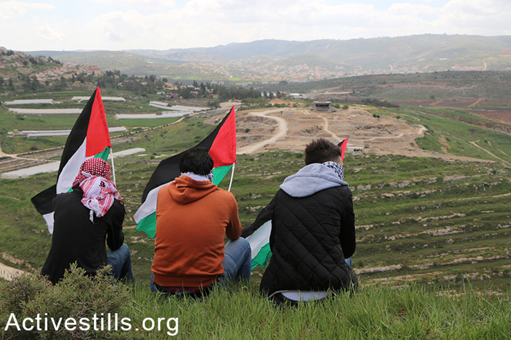 Palestinians raise their flag over the West Bank village of Qariyut. The Israeli settlement Shilo can been seen on the other hillside. All Israeli settlements in occupied Palestinian territory are illegal under international law. (photo: Activestills.org)