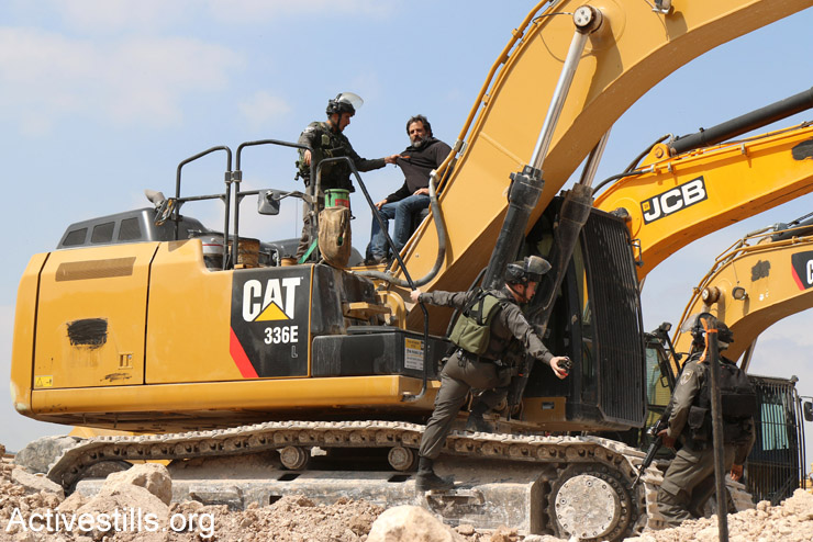 An Israeli activists climbs onto a tractor at a protest against Israeli plans to build new settlements in the E1 area of the West Bank, Eizariya, West Bank, March 17, 2015. (Ahmad al-Bazz/Activestills.org)