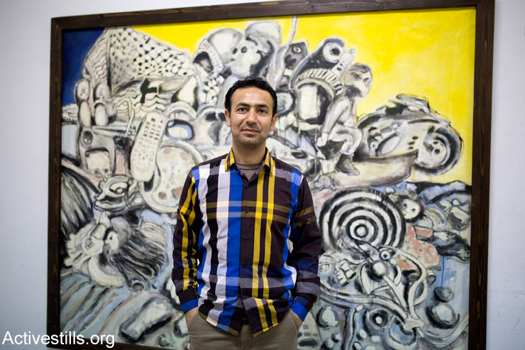 "Gaza Strip artist Raed Issa during the opening of his exhibition, ""Simple Dreams,"" in the Eltiqua Gallery in Gaza City, March 23, 2015. The exhibit included some of his destroyed paintings that he salvaged from the ruins of his home. Issa's home, which included his studio, was destroyed by an Israeli attack last summer. Raed lost many paintings and art materials."