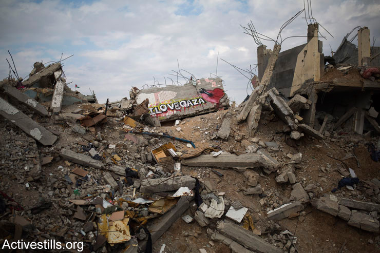 Graffiti is seen in on rubble in the destroyed quarter of Shujaiya, east of Gaza City, March 21, 2015. The rubble is being recycled to produce low quality concrete.