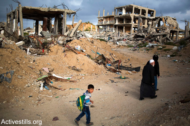Palestinians walk through a destroyed quarter of Al-Shaaf neighborhood, in Al-Tuffah, east of Gaza City, March 21, 2015. Tens of thousands of Palestinians are still internally displaced and many are living in very dire conditions.