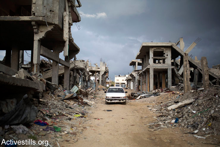 Palestinians drive through a destroyed quarter of Al Shaaf neighborhood, in Al Tuffah, east of Gaza City, March 21, 2015.