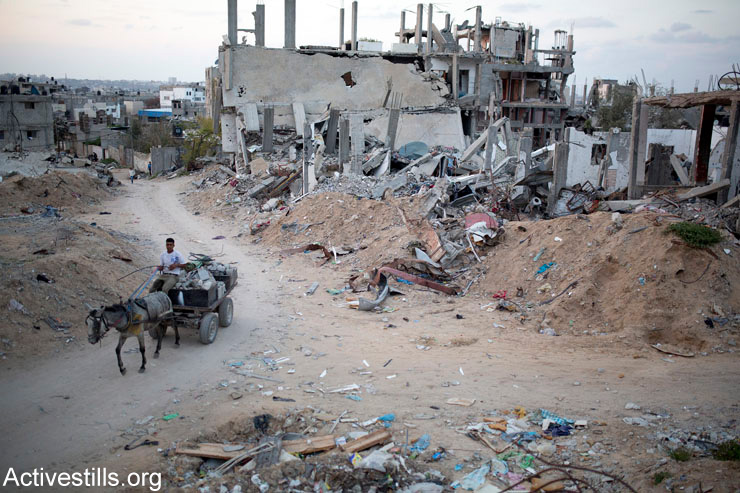 A Palestinian removes rubble from a destroyed quarter of Al Shaaf area, in Al Tuffah, east of Gaza City, March 21, 2015. The rubble is then recycled to produce low quality concrete for reconstruction.