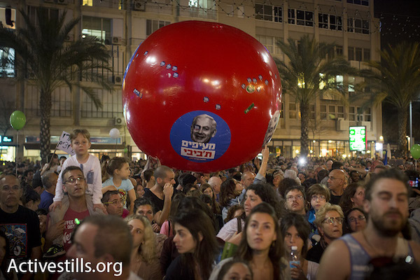 Israelis at a rally calling to oust PM Netanyahu, people toss a large ball with Netanyahu's likeness on it that reads, 'throwing [out] the Bibi', Rabin Square, Tel Aviv, March 7, 2015. (Photo by Oren Ziv/Activestills.org)