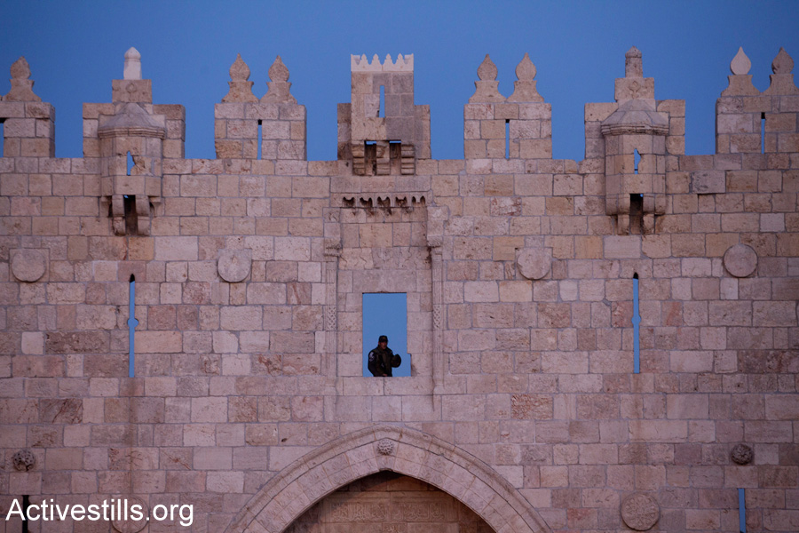An Israeli Border Police officer stands guard above Damascus Gate in East Jerusalem. The area often sees demonstrations and clashes between Palestinian residents of East Jerusalem and Israeli police. (Activestills.org)