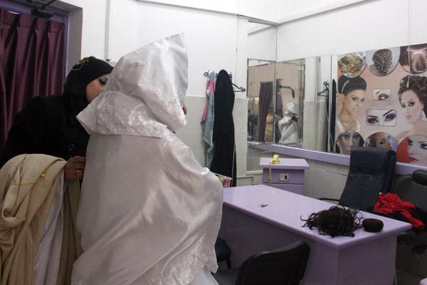 Haya Assad tries on her wedding dress in a Gaza City shop. (Photo by Abeer Ayyoub)
