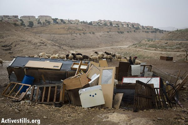 A sheep shelter constructed out of old furniture in a Bedouin camp in the E1 area, situated between Jerusalem and the Israeli West Bank settlement of Maale Adumim (background). (Photo: Oren Ziv/Activestills.org)