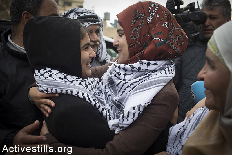 Palestinian Malak Al-Khateb, 14, is welcomed by family members, as she arrives to Beitin village near Ramallah, after being released from an Israeli prison, February 13, 2015. Al-Khateb, from Beitin village near Ramallah, was taken prisoner on December 31, 2014, and was subjected to interrogation and harsh treatment without legal representation. She had been accused of throwing stones at Israeli soldiers. On January 22, she was sentenced for two months in prison and a family was fined with 6,000 shekels fine ($1523). By the end of 2014, there were 197 children still imprisoned by Israel. Oren Ziv / Activestills.org