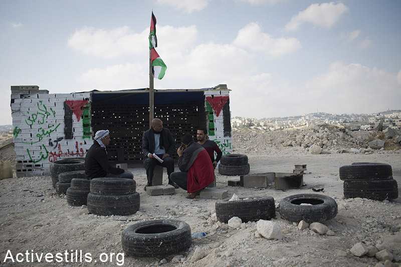 """Palestinian activists sit in the """"Gate of Jerusalem"""" protest camp near the West Bank Abu Dis town, is seen on February 9, 2015. The camp, which was demolished four times by the Israeli army, was set up to protest Israel's plan to confiscate lands in the E1 area, and to force the Jehalin Bedouins to move to the area of a garbage dump. Oren Ziv / Activestills.org"""