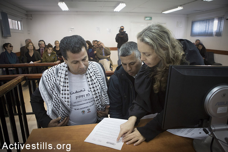 Israeli attorney Gabi Lasky speaks with Palestinian activist Abdullah Abu Rahmeh, before the beginning of his hearing in Ofer military court, West Bank, February 8, 2015. Oren Ziv / Activestills.org