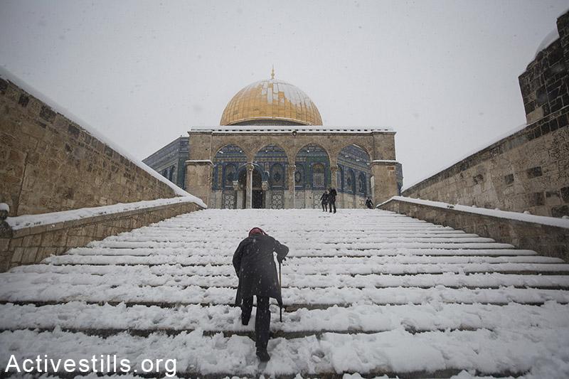 A Palestnian man walks Al Aqsa mosque at Jerusalem's old city following a snow storm, on February 20, 2015. Faiz al-Bazz / Activestills.org