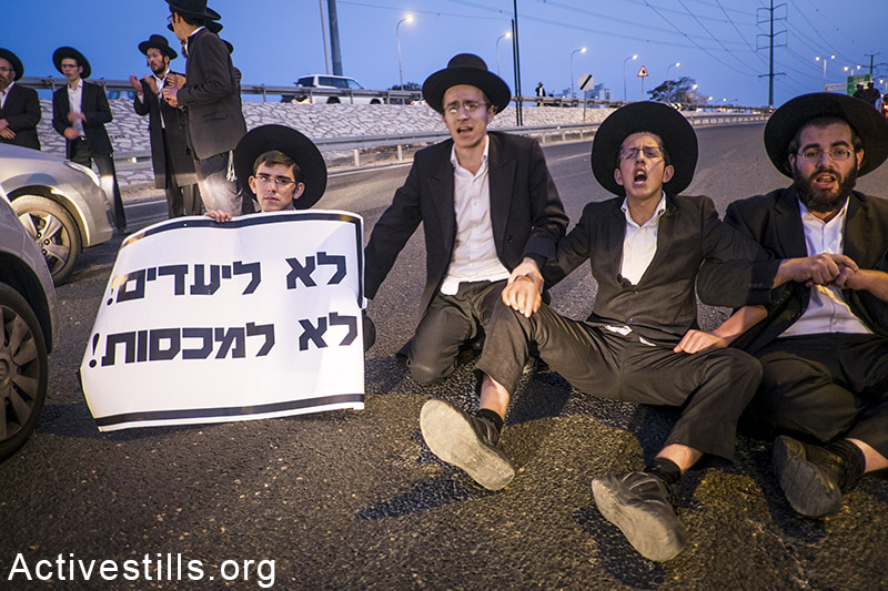 Ultra-Orthodox Jews participate in a protest in solidarity with four ultra-Orthodox youths who were detained last week for refusing to report to a military recruitment, near the city of Beni Brak, February 9, 2015. Yotam Ronen / Activestills.org