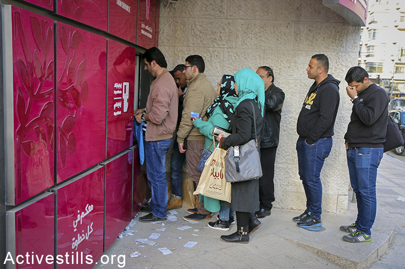 Palestinian public-sector workers stand in que for their salaries in Nablus city, West Bank, February 9, 2015. Yesterday, PA announced it will pay only 60% of January's salaries (Minimum of 2000 NIS). On the middle of January, workers also received 60% of their salaries of December. The future of the rest of the salaries is still unknown. The PA is in a midst of a financial crisis after the Israeli's decision of January 3rd, 2015, to freeze transfers of tax funds in response to Mahmoud Abbas' move to call on the ICC to pursue war-crimes charges against Israel. PA's salaries are estimated in around $200 million per month, $120 million of which is covered from the taxes collected by Israel. Ahmad al-Bazz / Activestills.org