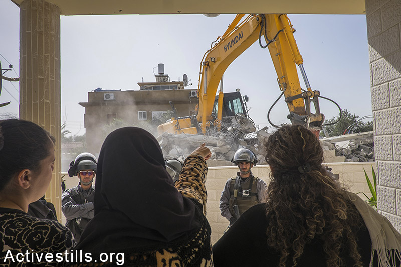 Israeli police officers stand guard as the home of Hana al-Nakib and her four children is being demolished, in the city of Lod, February 10, 2015. The house was built with the help of family members and neighbours who donated money to help the single mother. The house was built on a family-owned land, but without permission from the Israeli authorities. Palestinian citizens of Israel can hardly attain building permits due to Israel's discriminative criterions. Oren Ziv / Activestills.org