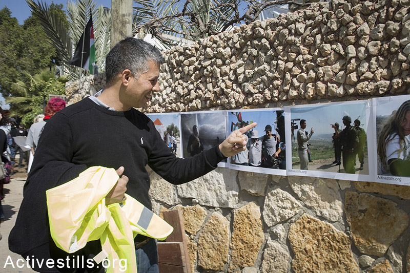 Muhammed Khatib, a Palestinian activist with the Popular Committees in Bil'in, stands near his photo taken in 2005, at an Activestills exhibition during a protest marking ten years for the struggle in against the Wall in the West Bank village Bil'in, February 27, 2015. The exhibition presented photos taken by Activestills photographers during the protests in the last ten years in the village. Shiraz Grinbaum / Activestills.org