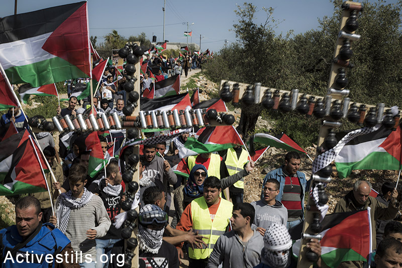 Palestinian activists march during a protest marking ten years for the struggle against the Wall in the West Bank village Bil'in, February 27, 2015. Keren Manor / Activestills.org