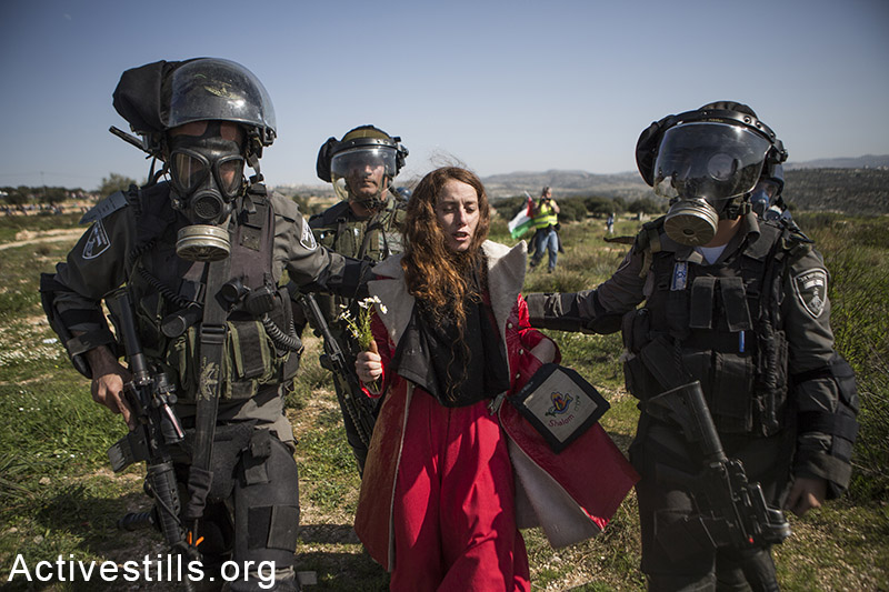 Israeli border policemen arrest an Israeli protester during a protest marking ten years for the struggle against the Wall in the West Bank village Bil'in, February 27, 2015. Yotam Ronen / Activestills.org