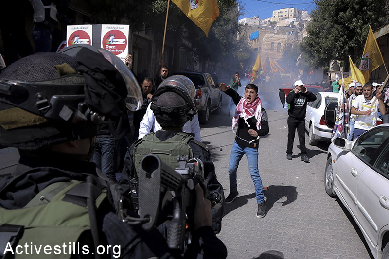 Palestinians protest against the closure of Shuhada Street, Hebron, West Bank, February 27, 2015.  Hundreds of Palestinians and internationals gathered on Friday marking the 21th anniversary of the street's closure. Shuhada street was closed by the Israeli army in 1994 following the Hebron mosque massacre where Baruch Goldstein, an Israeli settler, went on a rampage inside Al Ibrahimi Mosque, killing 29 Palestinians. Ahmad al-Bazz / Activestills.org
