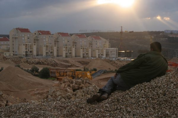 A Palestinian from the West Bank village of Bil'in looks out at the Modi'in Illit settlement bloc. (photo: Oren Ziv/Activestills.org)