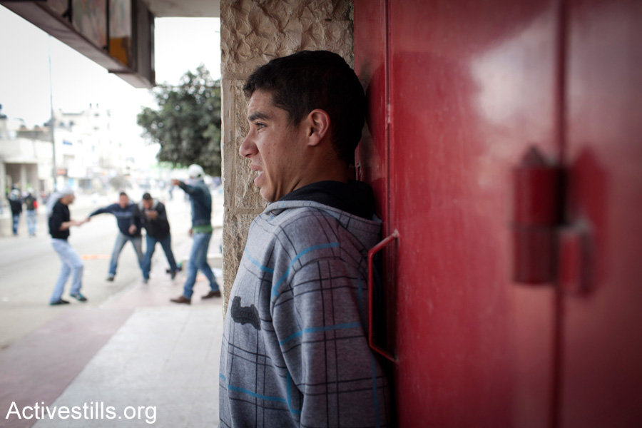 A Palestinian youth is caught in clashes between Israeli soldiers and Palestinian stone throwers. (Activestills.org)