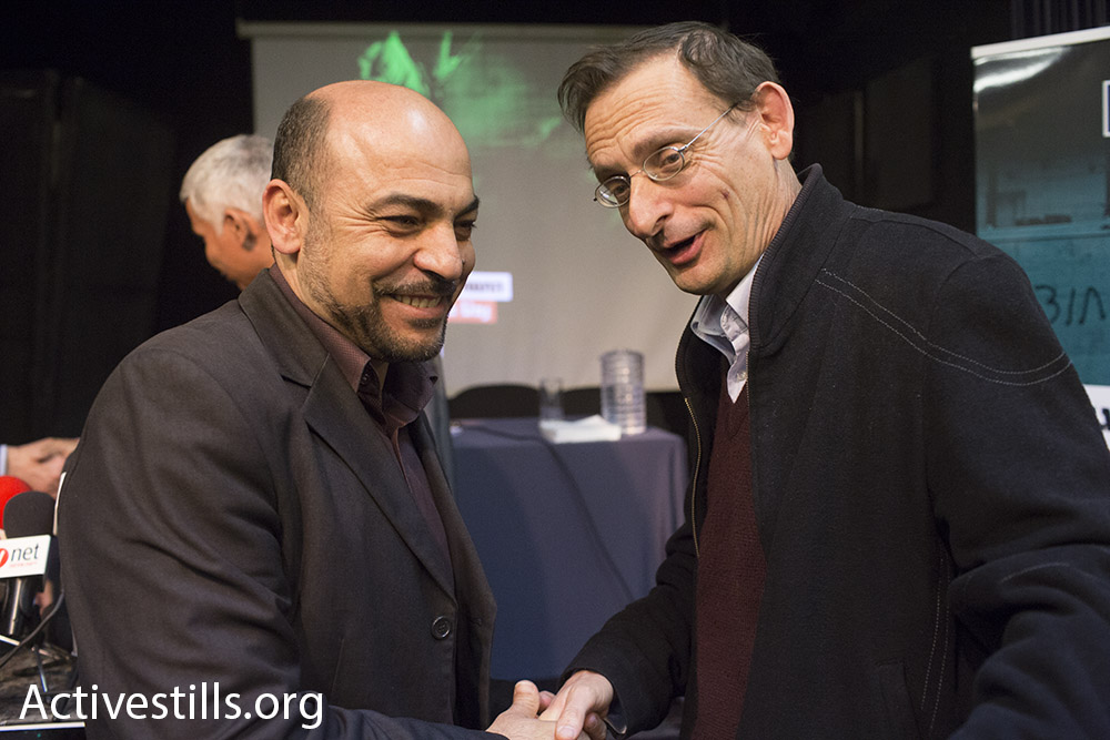 Masud Ganaim of Ra'am (left) shakes hands with Hadash's Dov Khenin. (photo: Oren Ziv/Activestills.org)