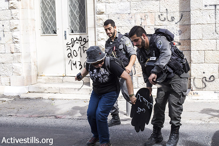 And Israeli policemen confiscates a sign from a protester during a demonstration against the Judaization of Sheikh Jarrah, East Jerusalem, March 27, 2015. (photo: Mareike Lauken, Keren Manor/Activestills.org)
