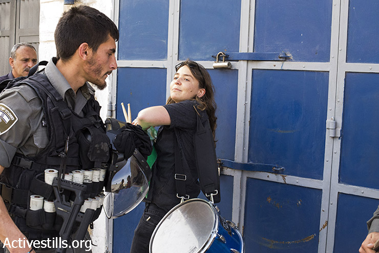 An Israeli policeman confronts an Israeli demonstrator during a march against the Judaization in the East Jerusalem neighborhood of Sheikh Jarrah, East Jerusalem, March 27, 2015. (photo: Mareike Lauken, Keren Manor/Activestills.org)