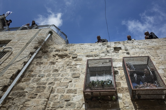 Settlers and Border Policemen stand on the roof of the Sub Laban family home, Old City of Jerusalem. (photo: Tali Mayer/Activestills.org)