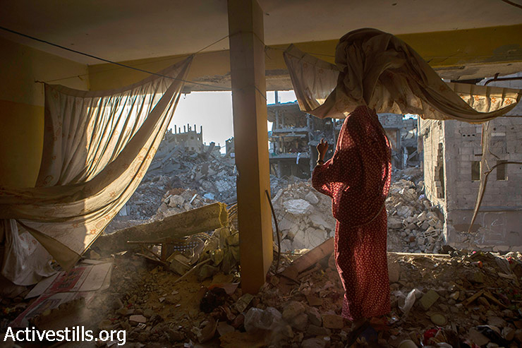 A Palestinian woman stands inside a damaged house in Shujayea neighborood, which was heavily damaged during the latest Israeli offensive, east of Gaza city, September 4, 2014. During the seven-week Israeli military offensive, 2,101 Palestinians were killed, including 495 children, and an estimated 18,000 housing units have been either destroyed or severely damaged, leaving more than 108,000 people homeless.