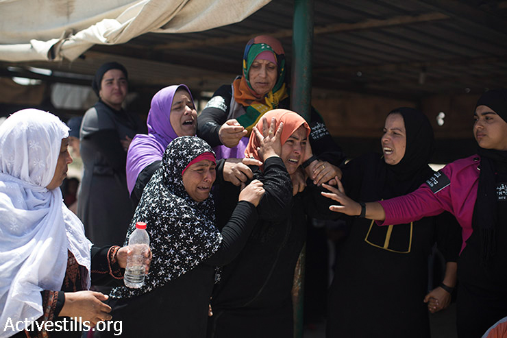 """Bedouin women cry as they watch the demolition of their house during the demolition of the """"unrecognized"""" Bedouin village of Al Araqib, in the Negev Desert, June 12, 2014. Israeli authorities demolished the village more than 70 times since 2010. On June 12, for the first time, Israeli forces entered the cemetery of the village, demolishing its mosque and all the houses, which local residents built after the first demolition in 2010."""