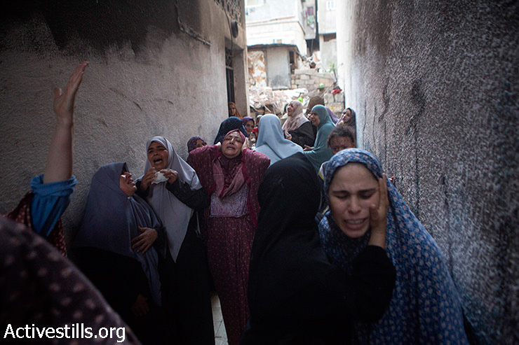 Palestinian women react during the funeral of the three children from Shuhaibar family killed earlier in an Israeli airstrike in the Sabra neighborhood of Gaza City, July 17, 2014. The three killed children were two brothers: Jihad Issam Shuhaibar (8), and Wasim Issam Shuhaibar (7) and their cousin Afnan Tariq Shuhaibar (10). The airstrikes came immediately after a temporary five-hour humanitarian ceasefire between Hamas and Israel ended.