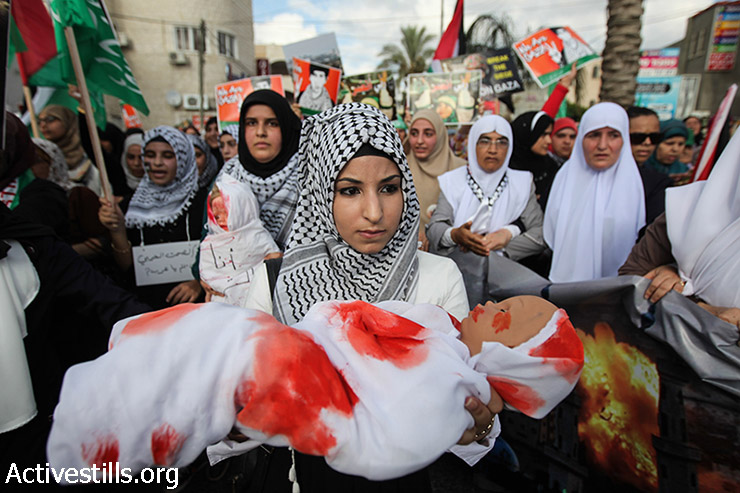 Palestinian ctitzens of Israel hold bloodied dolls during a demonstration against the Israeli attack on Gaza and in support of the Palestinian people, in the northern village Tamra, Israel, August 2, 2014.