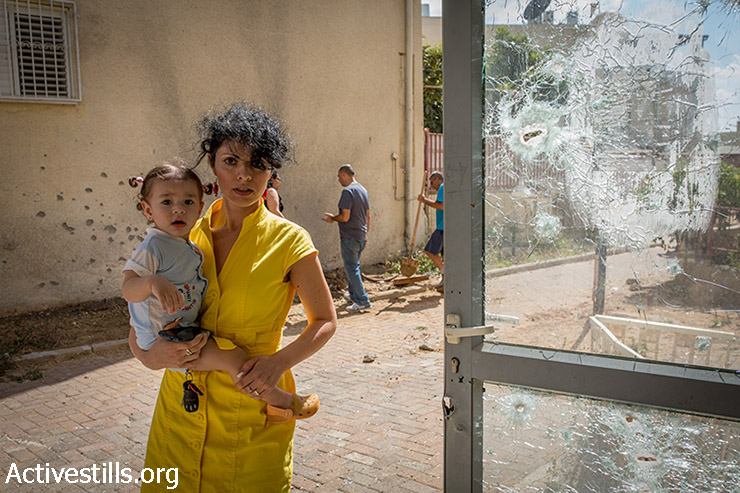 A woman and her baby stand near an area hit by a rocket launched from Gaza at the town of Sderot, Israel, on July 15, 2014.