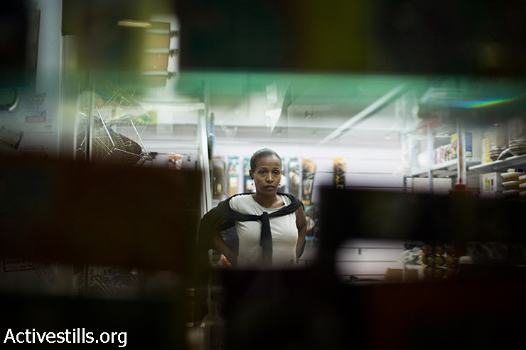 """An African asylum seeker looks out from her shop as residents of south Tel Aviv and right-wing nationalists protest against the Israeli supreme court's decision to cancel the """"Infiltrators Law"""" and to close Holot Detention Center, south Tel Aviv, October 5, 2014."""
