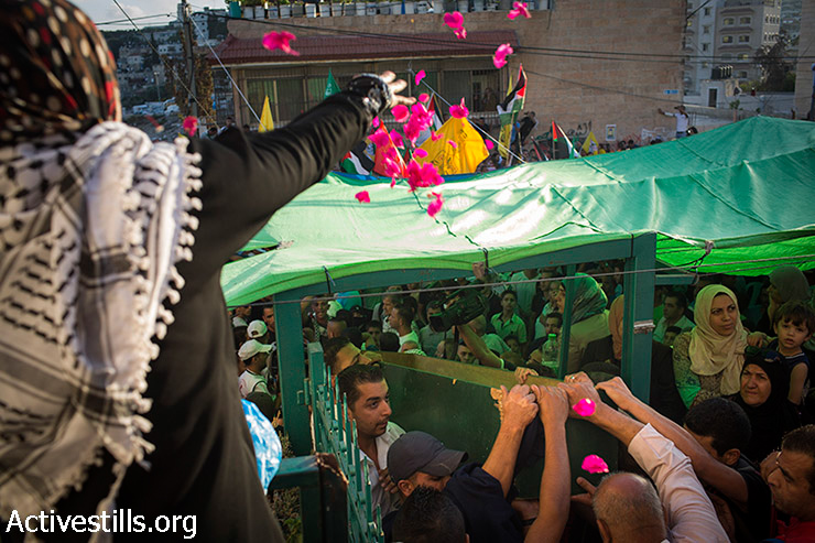 Palestinians carry the body of Mohammed Sinokrot during his funeral in the neighbourhood of Wadi Joz in East Jerusalem on September 8, 2014. Sinokrot, age 16, was wounded by police gunfire in the Wadi Joz neighbourhood on August 31 and died from his injuries on September 7.